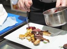De chef-kok verfraait geroosterd rek van lam Royalty-vrije Stock Afbeelding