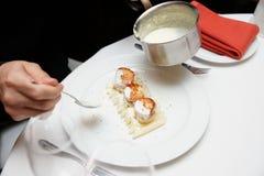 De chef-kok verfraait kammosselen met room Royalty-vrije Stock Foto's