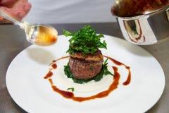 De chef-kok verfraait lapje vlees met saus Royalty-vrije Stock Afbeelding