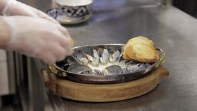 De chef-kok verfraait Oestersgroen en zet daarna toost van wit brood stock footage