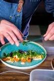 De chef-kok verfraait de salade met gerookte katvis, wortelen en miso sause Hoofdklasse in de keuken Het proces om te koken Stap  stock foto's