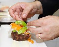 De chef-kok verfraait vlees Stock Foto
