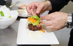 De chef-kok verfraait vlees Stock Afbeelding