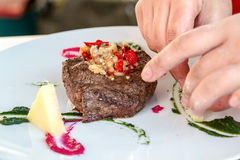 De chef-kok verfraait vlees Royalty-vrije Stock Fotografie