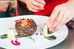De chef-kok verfraait vlees Royalty-vrije Stock Afbeelding