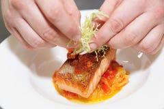 De chef-kok verfraait zalmlapje vlees Stock Foto's