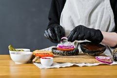 De chef-kok verzamelt ingrediënten van een cheeseburger r Eigengemaakt hamburgerrecept stock fotografie