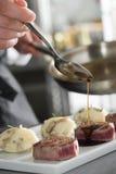De chef-kok voegt sause aan een rundvleeslapjes vlees toe, grijze backgroung Stock Foto