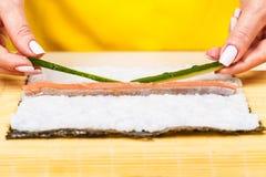 De chef-kok voegt verse komkommers toe Royalty-vrije Stock Fotografie