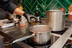 De chef-kok voegt witte wijn aan een schotel toe Stock Foto's