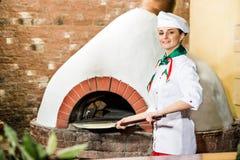 De chef-kok zet deeg in de oven voor pizza's, Royalty-vrije Stock Foto's
