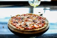 De chef-kok zet sesamolie aan bovenste laagje van pizza Het heeft aardige geur of goede geur Hij kookt bij keuken Het kijkt zo sm royalty-vrije stock foto