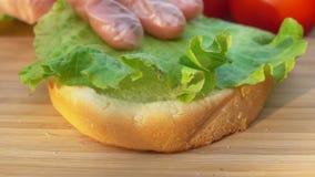 De chef-kok zet slablad op een broodje