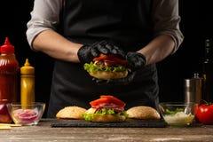 De chef-kok zet tomatenringen op een hamburger, op de achtergrond van de ingrediënten Horizontale foto, Smakelijk en ongezond voe stock afbeeldingen
