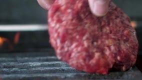 De chef-kok zet verse handen van het vlees voor de Hamburger op de grill