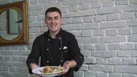 De chef-kok in zwarte eenvormig stelt smaaksalade op witte bakstenen muurachtergrond 4k voor stock video