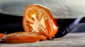 De chef-kok in zwarte handschoen snijdt ringen van rode ronde tomatenringen, ingrediënt voor een hamburger stock footage