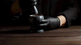 De chef-kok in zwarte latexhandschoenen houdt een steenmortier met een mengsel van peper stock videobeelden