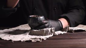 De chef-kok in zwarte latexhandschoenen houdt een steenmortier met een mengsel van peper, kokende en malende kruiden stock video