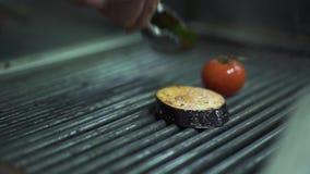 De chef-kokhand zet groententomaat, aubergine, gele groene paprika op de grill dicht uitputtend metaaltang Kok het voorbereidinge stock videobeelden