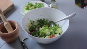De chef-kokhanden gieten olijfolie en balsemieke azijn, groene salade stock video