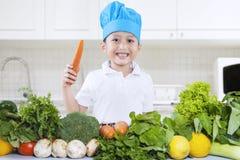 De chef-kokjongen kookt groenten Stock Afbeelding