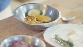 De chef-koks dient zwarte latexhandschoenen in marineren groenten: graan en plakken van courgette in de kom stock footage