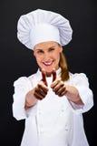 De chef-kokvrouw toont o.k. teken over donkere achtergrond Royalty-vrije Stock Afbeeldingen