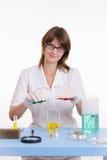 De chemicus mengt de twee vloeistoffen Royalty-vrije Stock Afbeeldingen