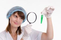 De chemicus onderzoekt vloeistof in een reageerbuis Stock Afbeeldingen