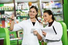 De chemicusvrouwen van de apotheek in drogisterij stock afbeeldingen