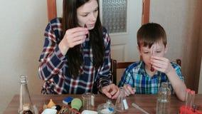 De chemie experimenteert thuis Het mamma en de zoon doen een experiment met rood verf en water stock video