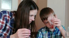 De chemie experimenteert thuis Het mamma en de zoon doen een experiment met rood verf en water stock footage