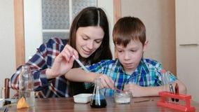 De chemie experimenteert thuis Het mamma en de zoon maken een chemische reactie met de versie van gas in de fles stock videobeelden