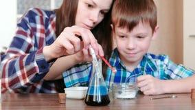 De chemie experimenteert thuis Het mamma en de zoon maken een chemische reactie met de versie van gas in de fles stock footage
