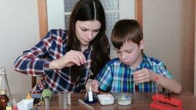 De chemie experimenteert thuis Het mamma en de zoon maken een chemische reactie met de versie van gas in de reageerbuis stock footage