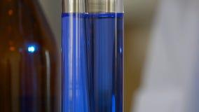 De Chemische producten van wetenschapperpours blue pattern in in Fles Gezondheidszorg en medisch concept De wetenschapper is bepa royalty-vrije stock afbeeldingen