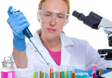 De chemische vrouw die van de laboratoriumwetenschapper met pipet werkt stock afbeeldingen