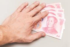 De Chinese 100 bankbiljetten van de yuansrenminbi en mannelijke hand Stock Afbeelding