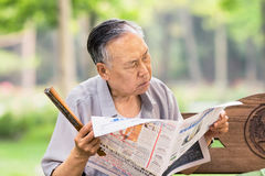 De Chinese mannelijke oudste leest een krant in een park, Peking, China Stock Afbeeldingen