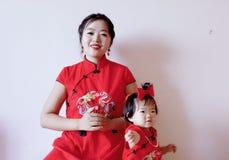 De Chinese moeder en het kind in rode cheongsam doen goed geluk stellen stock afbeeldingen