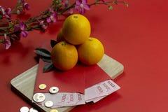 De Chinese nieuwe jaar verse sinaasappelen en angpao in eigen zak steken met houten raad en kersenbloesembloem op rode document a stock foto