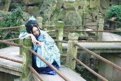 De Chinese vrouw in traditionele Blauwe en witte Hanfu-kleding beklimt op het traliewerk royalty-vrije stock afbeeldingen