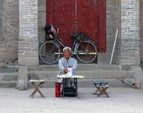 De Chinese zitting van de fortuinteller bij de ingang aan een Boeddhistisch klooster Royalty-vrije Stock Afbeeldingen