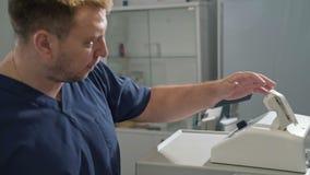 De chirurg in een witte steriele peignoir werkt in het ziekenhuis met medische apparatuur Een arts in klinisch stock footage