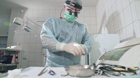 De chirurg gekleed in een robe en een masker neemt medische instrumenten van de sterilisatieapparaten en werpt binnen een klem stock footage