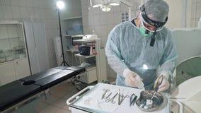 De chirurg in het ziekenhuis desinfecteert de medische instrumenten vóór de verrichting Arts in professionele glazen, stock footage