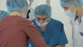 De chirurgen werken Het team die van de reanimatiegeneeskunde maskers dragen die medische hulpmiddelen houden stock footage