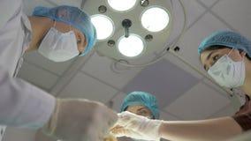 De chirurgen werken Het team die van de reanimatiegeneeskunde maskers dragen die medische hulpmiddelen houden stock videobeelden
