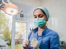 De chirurgentandarts die in de forceps van de maskerholding voor tandextractie bij kliniek voorbereidingen treffen Stock Afbeeldingen